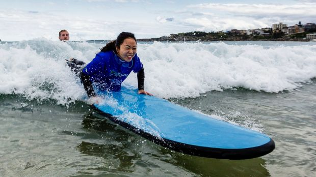 Xiaodan Zhang gets a surfing lesson in Bondi as part of a push to attract more middle class Chinese tourists.