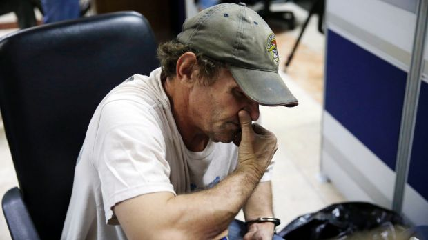 David Timothy Deakin is handcuffed to a chair at the National Bureau of Investigation in Manila, Philippines, on April ...