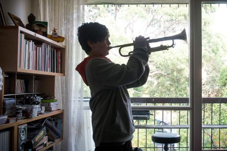 MELBOURNE, AUSTRALIA - MAY 14: Young boy Sidney practices the trumpet and piano at home in Fitzroy on May 14, 2017 in ...