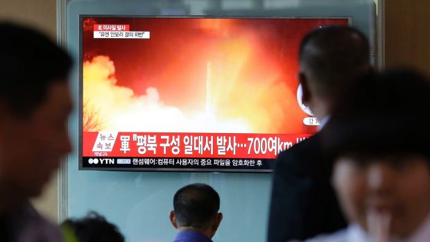 South Korean commuters at Seoul Railway Station watch footage of this week's missile launch.