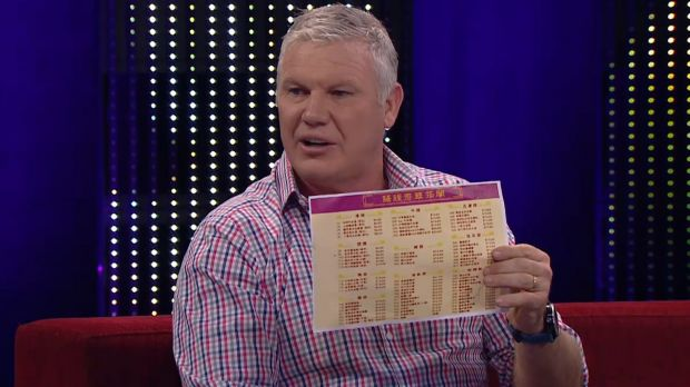 Bounce host Danny 'Spud' Frawley holding a Chinese menu while mocking the historic Shanghai AFL game.