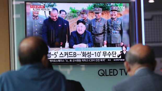 People in South Korea watch a TV news program showing an image of North Korean leader Kim Jong-un on Monday.