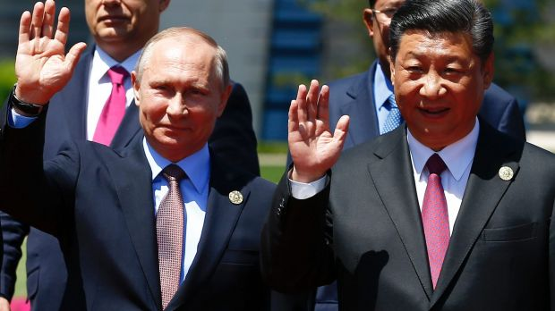 Chinese President Xi Jinping, right, and Russian President Vladimir Putin wave at the Belt and Road Forum on Yanqi Lake ...