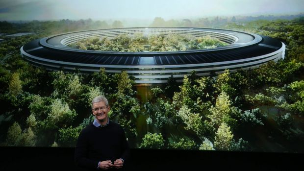 Apple CEO Tim Cook speaks in front of an artist's impression of the new campus, Apple Park.