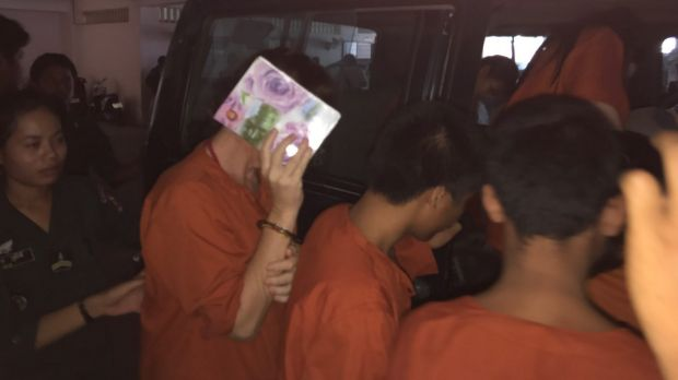 Tammy Davis-Charles hides her face as she is led back to her jail cell from the court in Phnom Penh in May.