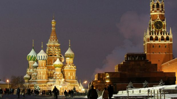 People walk in Red Square, with St. Basil Cathedral, left, the Kremlin's Spassky Tower, right.