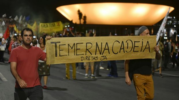 """Demonstrators carry a sign that reads in Portuguese """"Temer in jail"""" and calls for direct elections in Brasilia on Thursday."""