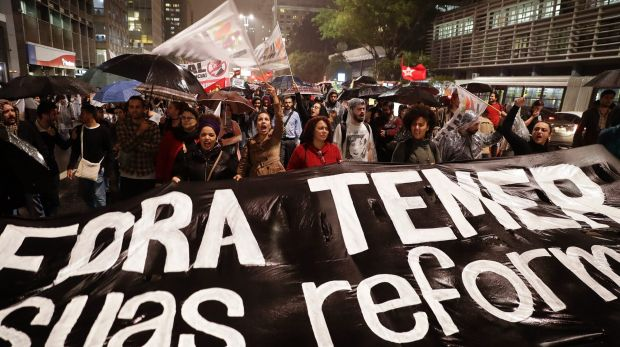 """Demonstrators march carrying a banner that reads in Portuguese """"Get out Temer and your reforms"""" in Sao Paulo on Thursday."""