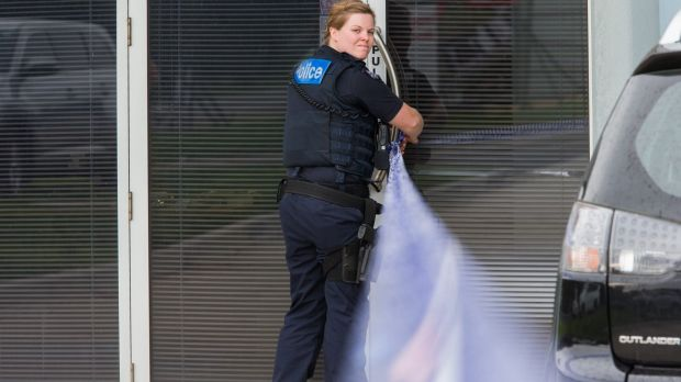 A police officer taping off the crime scene at the Braeside factory.