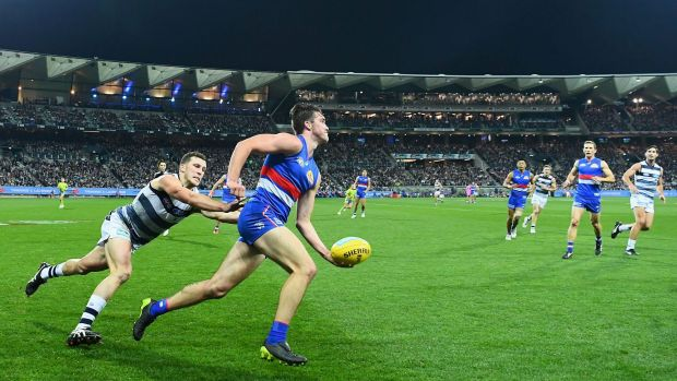 Opening night: Bulldog Bailey Williams looks to handball on Friday night with Geelong's new Brownlow Stand in the background.