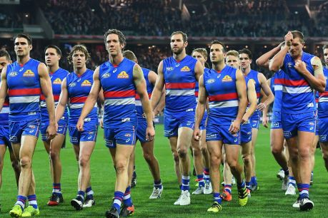 Body language: Dejected Bulldogs leave the ground after the loss to the Cats.