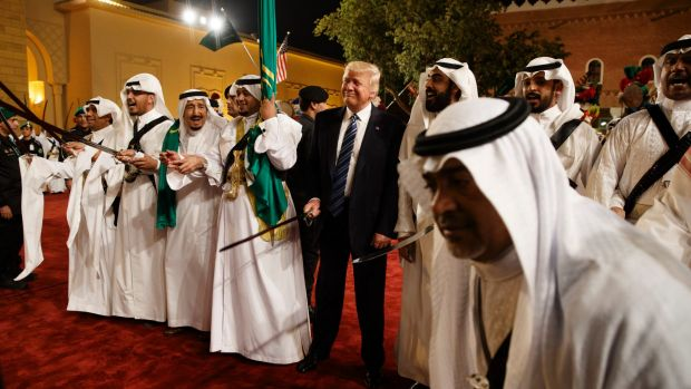 President Donald Trump holds a sword and sways with traditional dancers during a welcome ceremony in Riyadh.