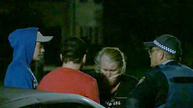 Police speak to people at the Kingswood home where a woman died on Sunday.