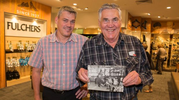 Troy (left) and Trevor (right) at Fulchers Shoes, holding a picture of Trevor's father, Gordon, at work.