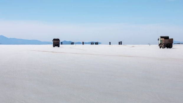 Trucks working on the production of lithium traverse the salt flats of Bolivia.