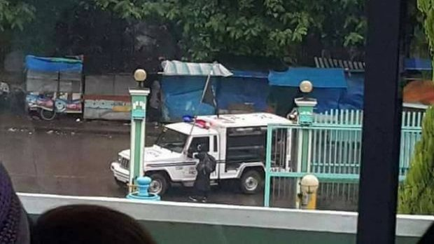 A seized police vehicle flies a black Islamic State-style flag on the streets of Marawi City on Tuesday.