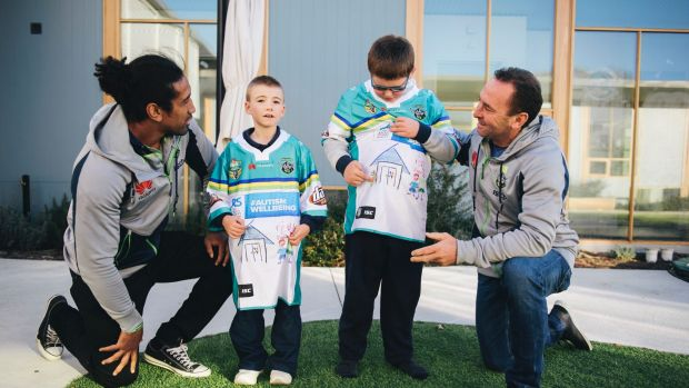 Sia Soliola and Ricky Stuart meet with Jayden, 8, and Max, 12, to give them the special jerseys they helped design.