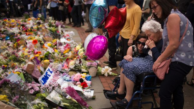 Women cry after placing flowers in a square in central Manchester, Britain, Wednesday, May 24, 2017, after the suicide ...