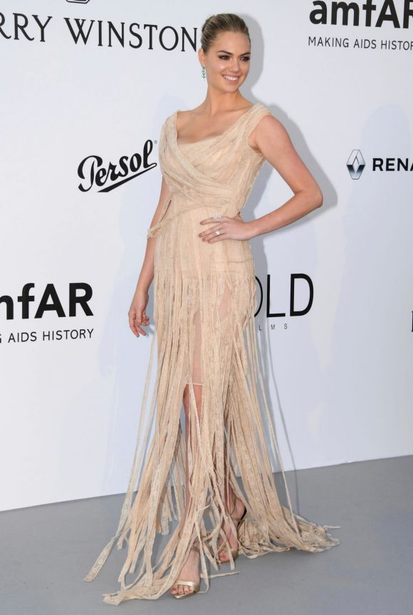 Model Kate Upton poses for photographers upon arrival at the amfAR charity gala in a shredded beige dress.