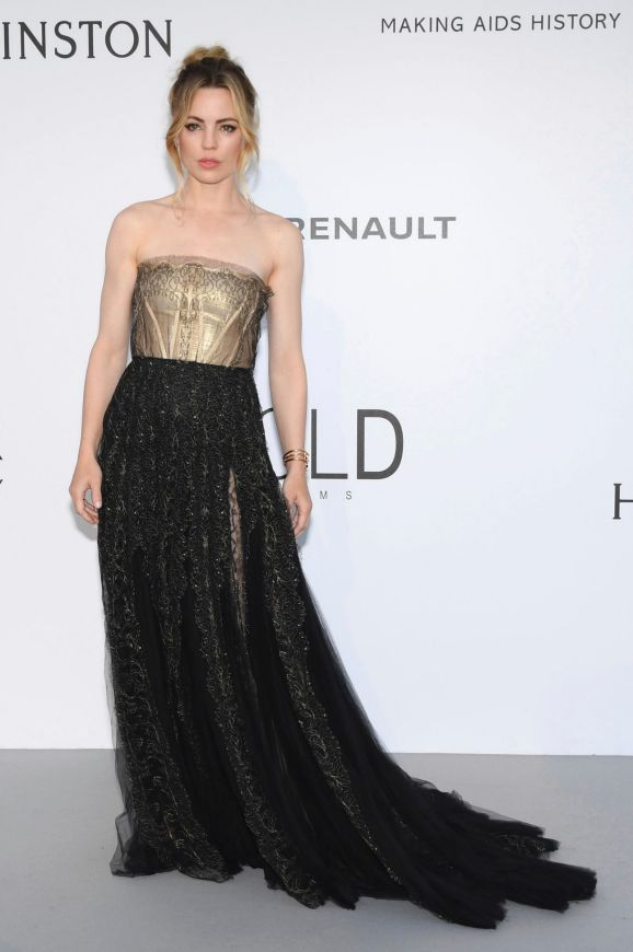 Actress Melissa George poses for photographers upon arrival at the amfAR charity gala in a gold and black floor length gown.