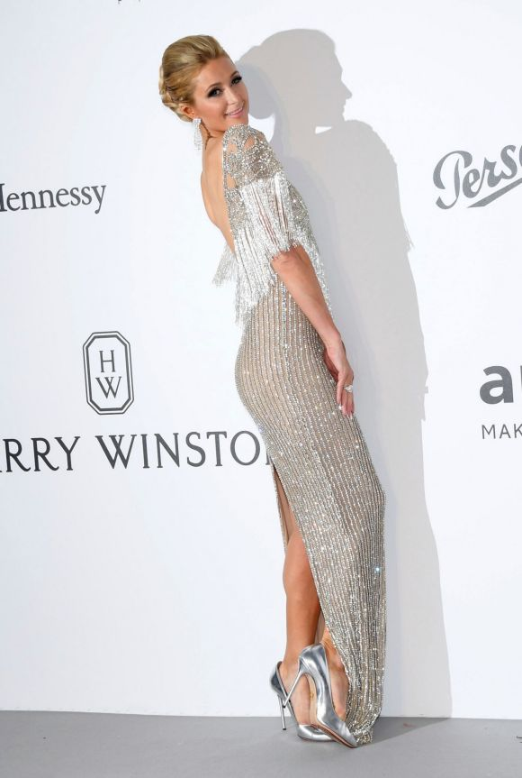 Heiress Paris Hilton poses for photographers upon arrival at the amfAR charity gala in a silver sequin gowns with ...