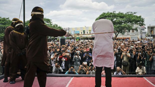 A Shariah law official whips one of two men convicted of gay sex during a public caning outside a mosque in Banda Aceh, Aceh.