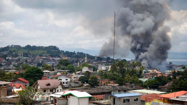 Smoke rises from houses following airstrikes by Philippine Air Force bombers as government forces battle to retake ...