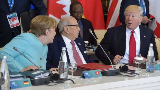 US President Donald Trump shares a word with German Chancellor Angela Merkel, as Tunisia's President Beji Caid Essebsi, ...