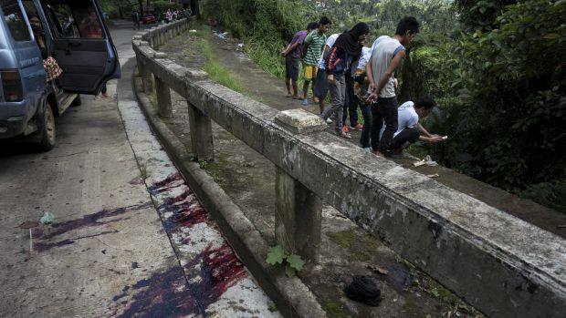 Blood stains the roadside as  civilians view bodies dumped in a ditch by militants. The eight executed men, who were ...