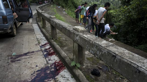 Blood stains the roadside as  civilians view unidentified bodies believed to have been executed and dumped in a ditch by ...