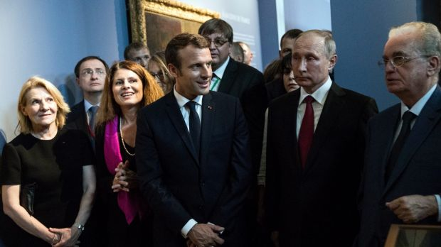 Emmanuel Macron, centre, and his Russian counterpart Vladimir Putin, 2nd right, visit an exhibition about Russian ...