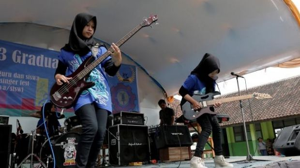 Widi Rahmawati (L) and Firdda Kurnia, members of the metal band Voice of Baceprot, perform during a school's farewell ...