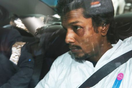 Alleged to have threatened to bomb Flight 128, Manodh Marks is taken from Tullamarine to the Melbourne Magistrates Court ...
