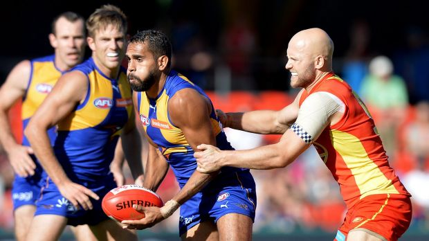 West Coast's Lewis Jetta is pressured by Gary Ablett, who starred for the Suns.