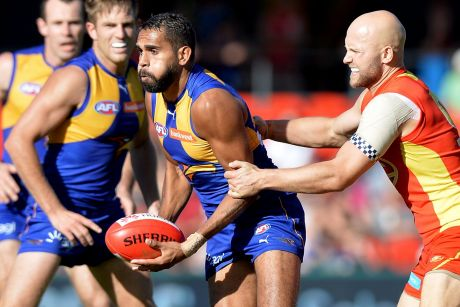 Lewis Jetta is pressured by the defence of Gary Ablett at Metricon Stadium.