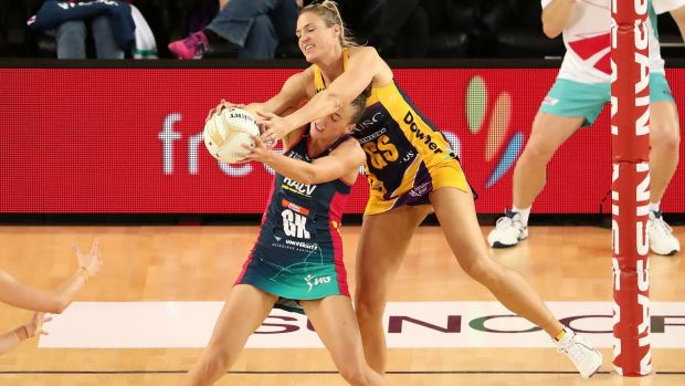 MVP Caitlin Bassett of the Lightning wrestles with Melbourne Vixens' Emily Mannix.