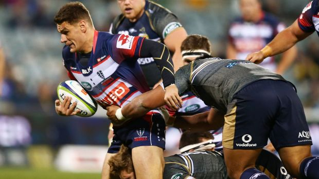 Mitch Inman of the Rebels is tackled by the Brumbies.