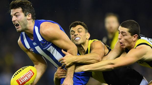 North Melbourne's Luke McDonald attempts to handball as Tigers Sam Lloyd and Jason Castagna apply pressure.