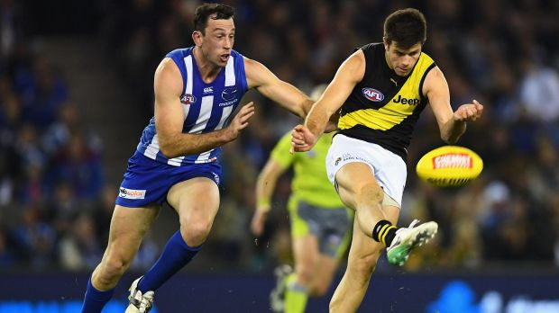 Richmond skipper Trent Cotchin gets his kick away as Roo ruckman Todd Goldstein gives chase.