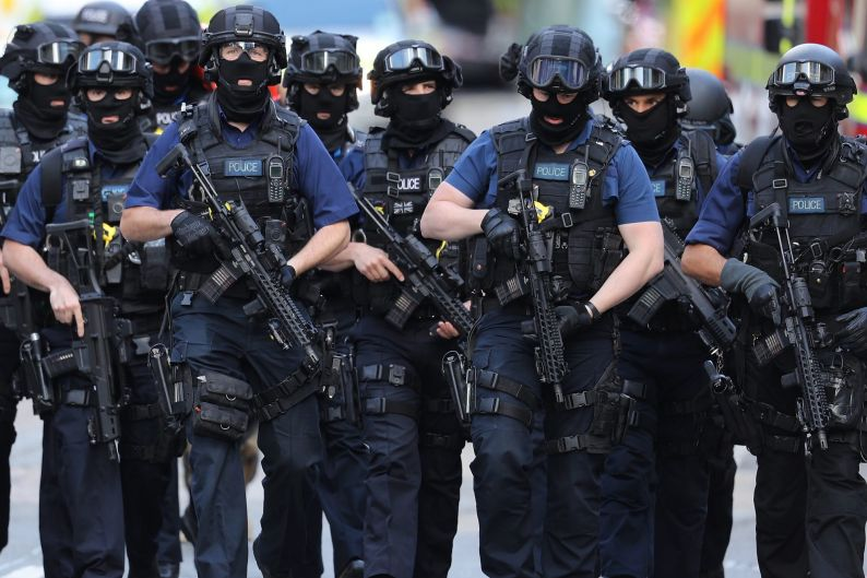 Counter terrorism officers march near the scene of last night's London Bridge terrorist attack in London, England.