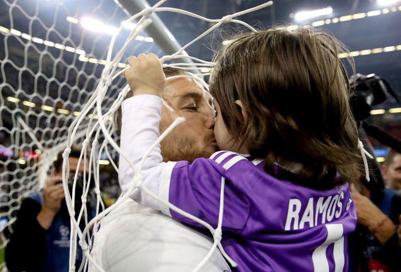 Real Madrid's Sergio Ramos celebrates with one of his children after winning the Champions League Final soccer match ...