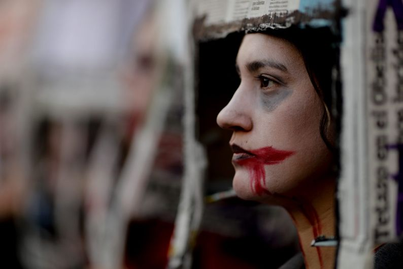 A woman with her face painted participates in a protest against gender violence, in Buenos Aires, Argentina. Under the ...