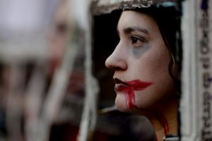 A woman with her face painted participates in a protest against gender violence, in Buenos Aires, Argentina, Saturday, ...