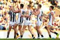 Pies procession: Collingwood players line up to congratulate Jamie Elliott on kicking a crucial goal against the Dockers.