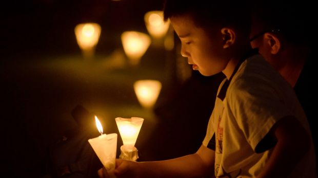 A young boy holds a candle during a candlelight vigil at Victoria Park in Hong Kong.