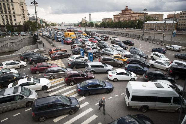A man crosses a street during a traffic jam on the embankment of the Moskva River in downtown Moscow, Russia.