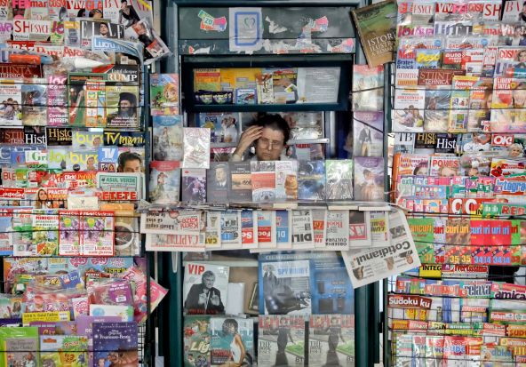 A newspaper vendor touches her forehead sitting in a kiosk at the main railway station, Gara de Nord, in Bucharest, Romania.