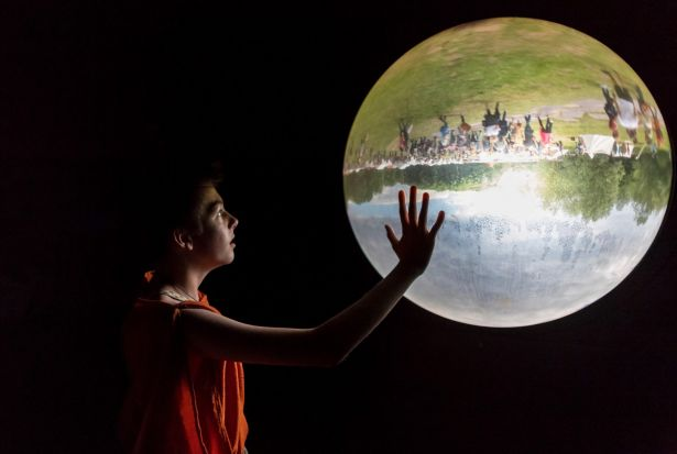 A boy looks at a glass bowl showing the outside upside down in a museum in Bramsche-Kalkriese, Germany.