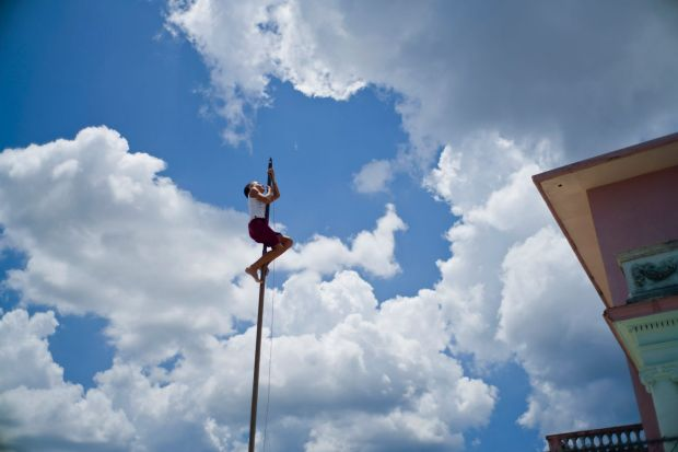 A child climbs a flag pole to repair the rope, at his school in Havana, Cuba.