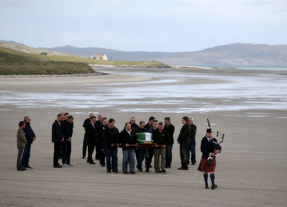 The coffin of Eilidh MacLeod draped in the Barra flag is carried across Traigh Mhor beach at Barra airport after it ...